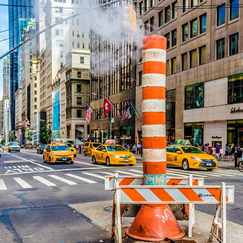 A typical streetview on the streets of New York City. Yellow Cabs and underground steam vents.