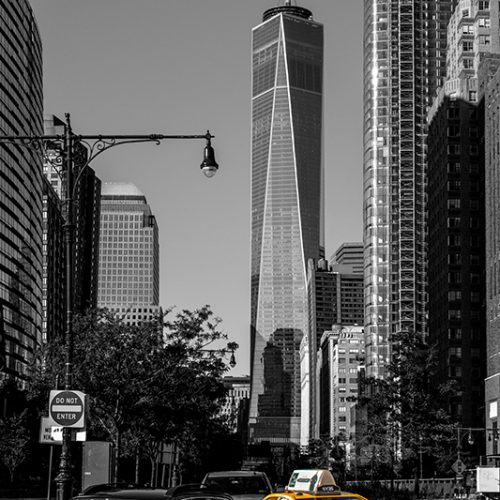 Streetview of a New York city yellow cab turning on a junction. In the background One World Trade
