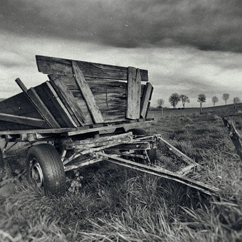 wet plate photograph of an old trailer in a field.